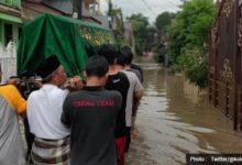 Photo of Beredar Foto Warga Gotong Keranda Jenazah di Tengah Banjir